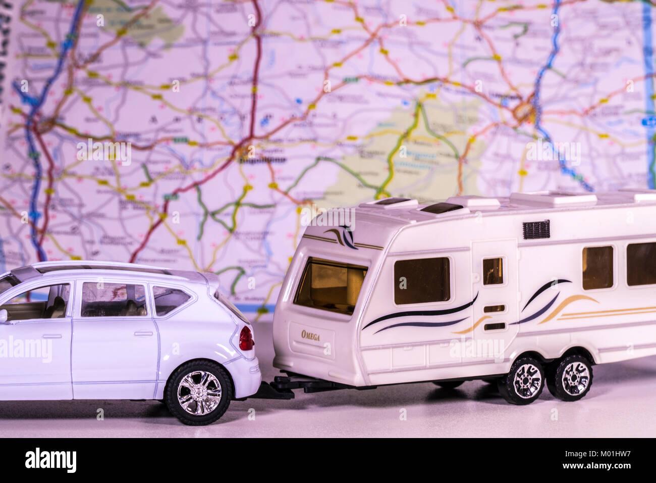 Caravana y modelo de coche con un mapa de desenfoque / atlas en el fondo. Concepto de cualquier aspecto de camping / touring / la libertad del camino abierto, etc. Foto de stock