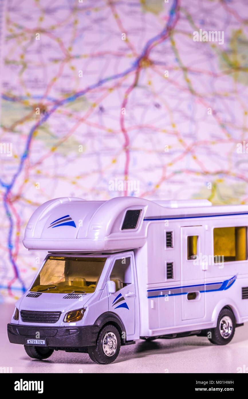 Modelo / autocaravana autocaravana con mapa de desenfoque / atlas en el fondo. Concepto de cualquier aspecto de camping / touring / la libertad del camino abierto, etc. Foto de stock
