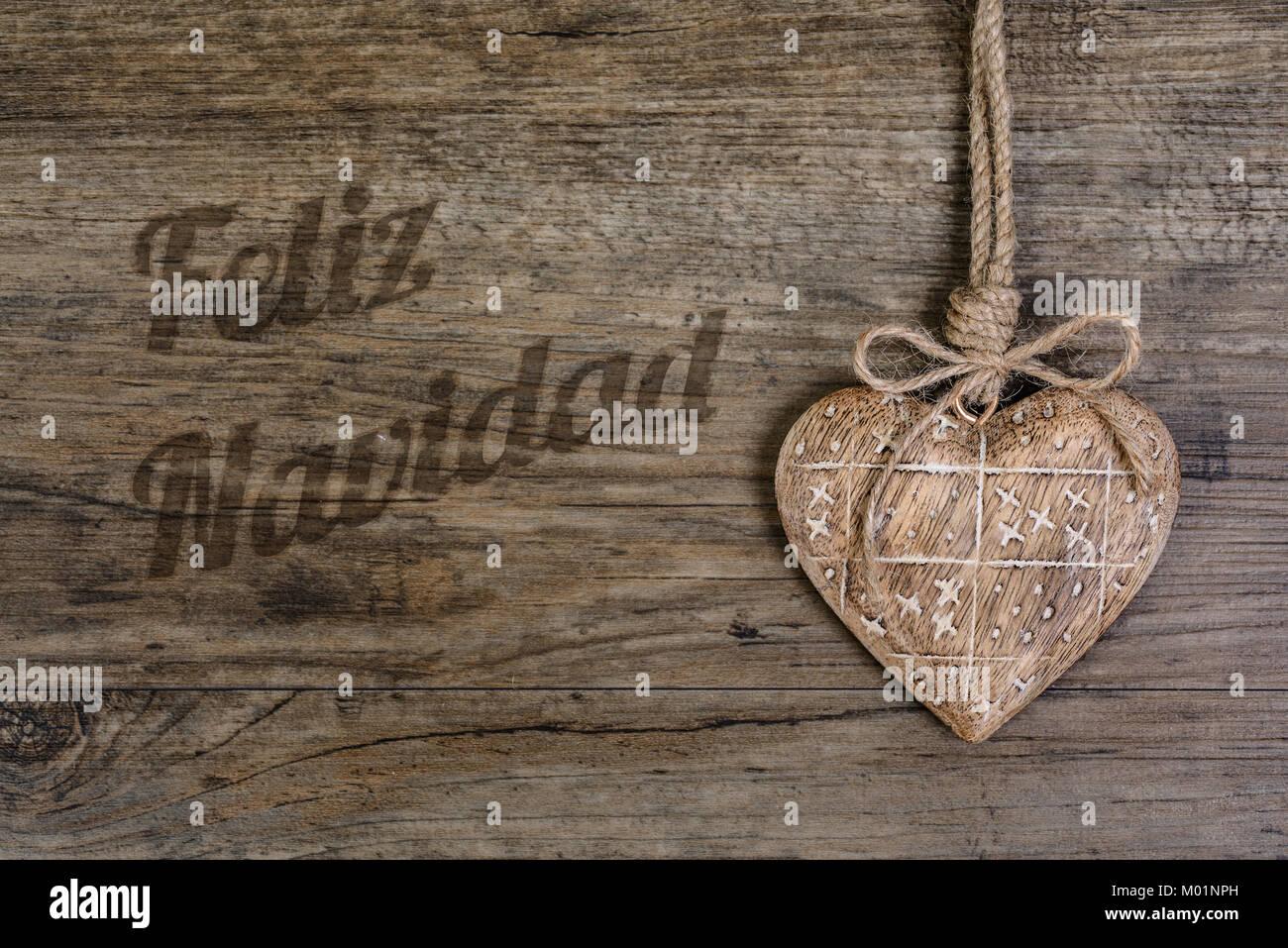 """""""Feliz Navidad"""" o """"Merry Christmas"""" en letras de quemado de madera con decoración de corazón Imagen De Stock"""