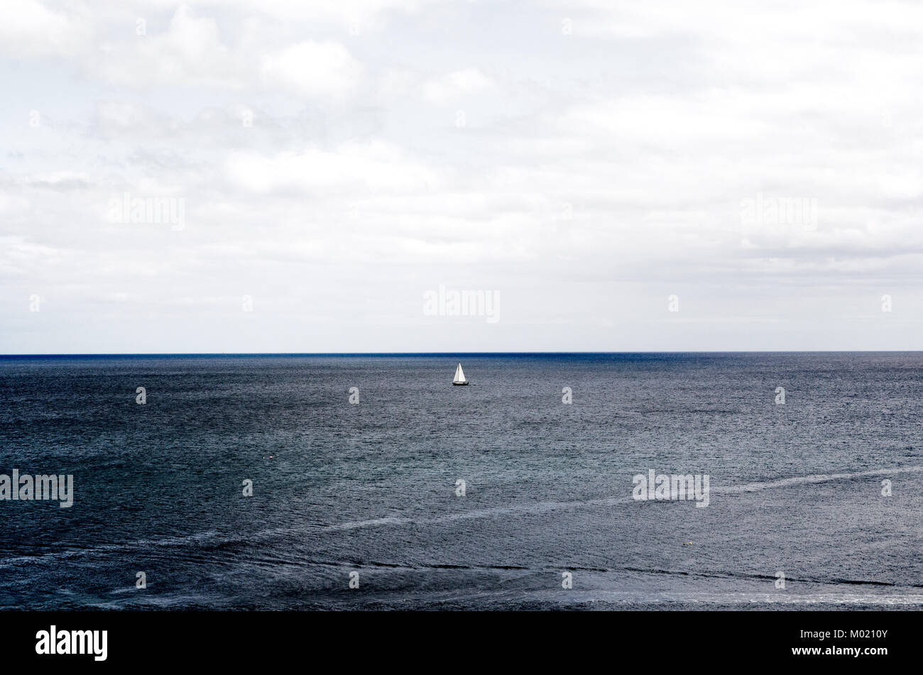 Bote de vela en el mar bajo el cielo nublado en la costa de Mevagissey, Cornwall Foto de stock