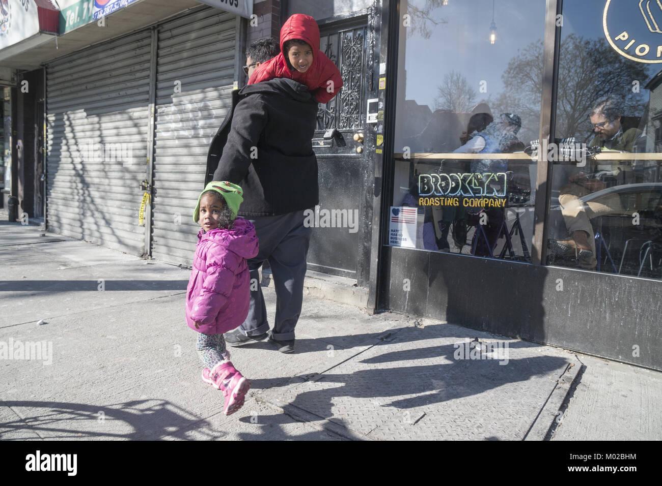 Padre remolca a sus hijos por la calle en la Iglesia Avenue en Brooklyn, NY. Imagen De Stock