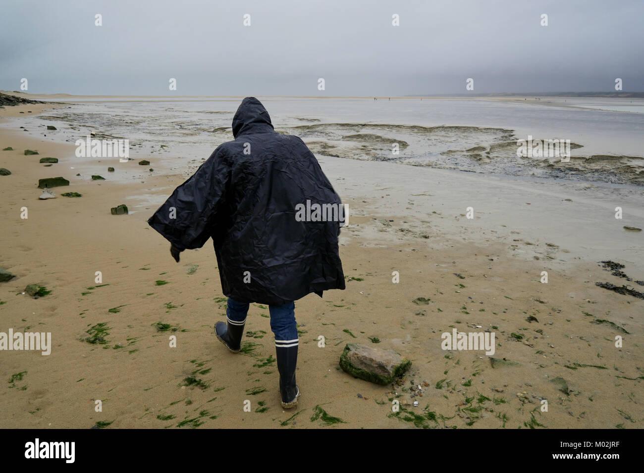 Un excursionista camina sobre la playa de arena a lo largo de la bahía de Somme, en marea baja, Le Hourdel, bahía de Somme, Normandía, Francia Foto de stock
