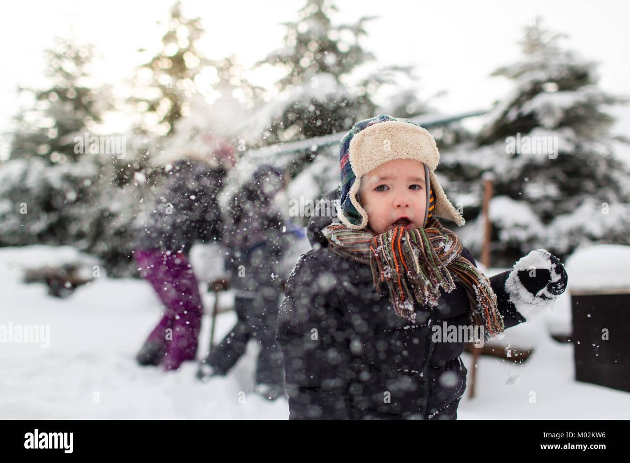 Vista frontal de un niño pequeño con la boca abierta y su familia lucha de bola de nieve en el fondo. Imagen De Stock