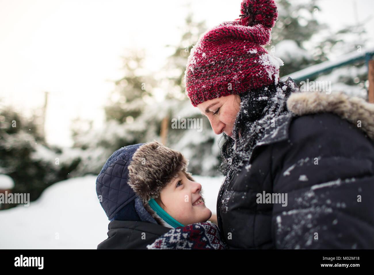 Vista lateral de una feliz madre e hijo mirándose a los ojos después de una pelea con bolas de nieve Imagen De Stock
