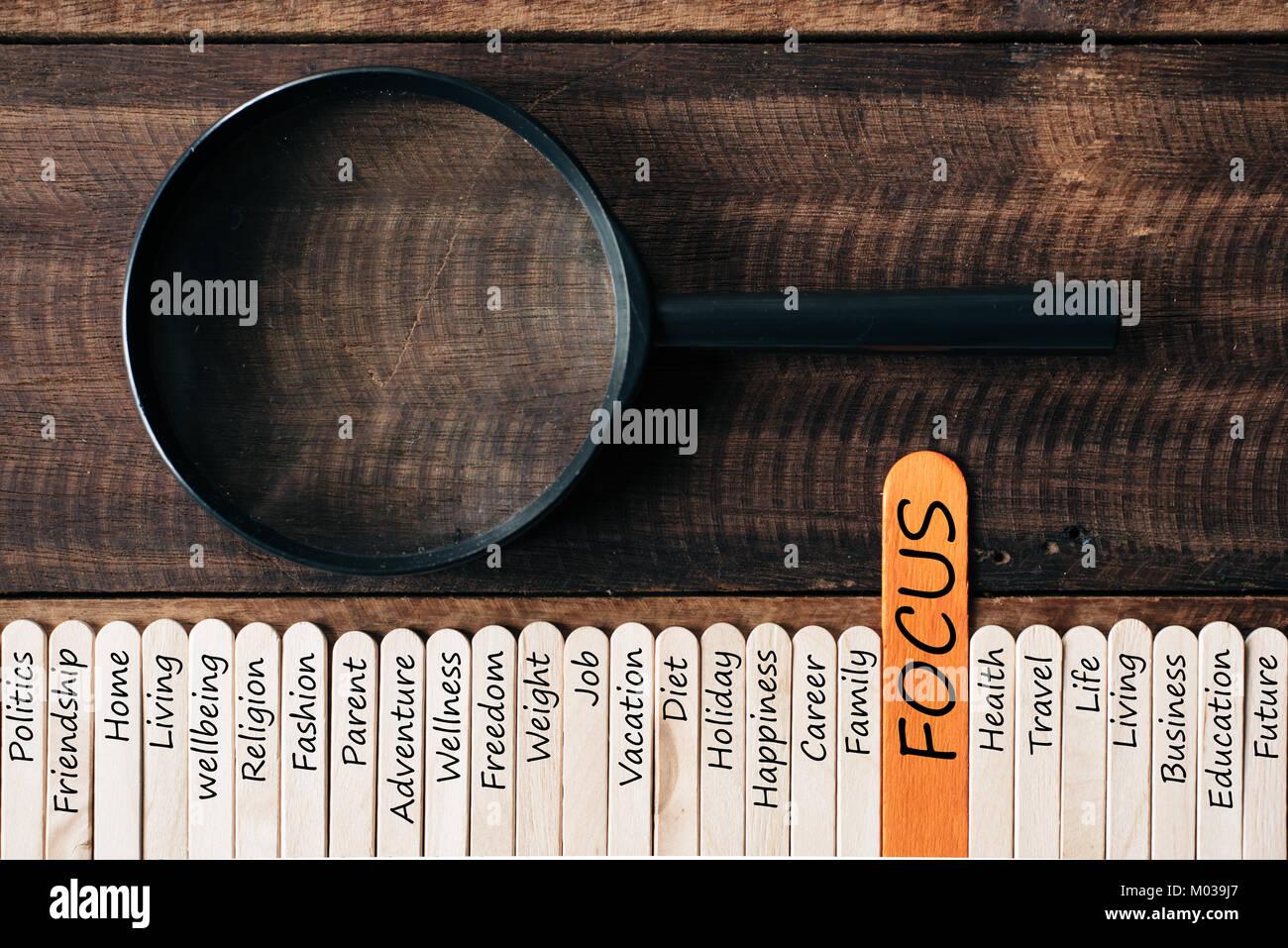 Lupa y palos de madera con el estilo de vida la palabra relacionada. centrarse en concepto de estilo de vida Foto de stock