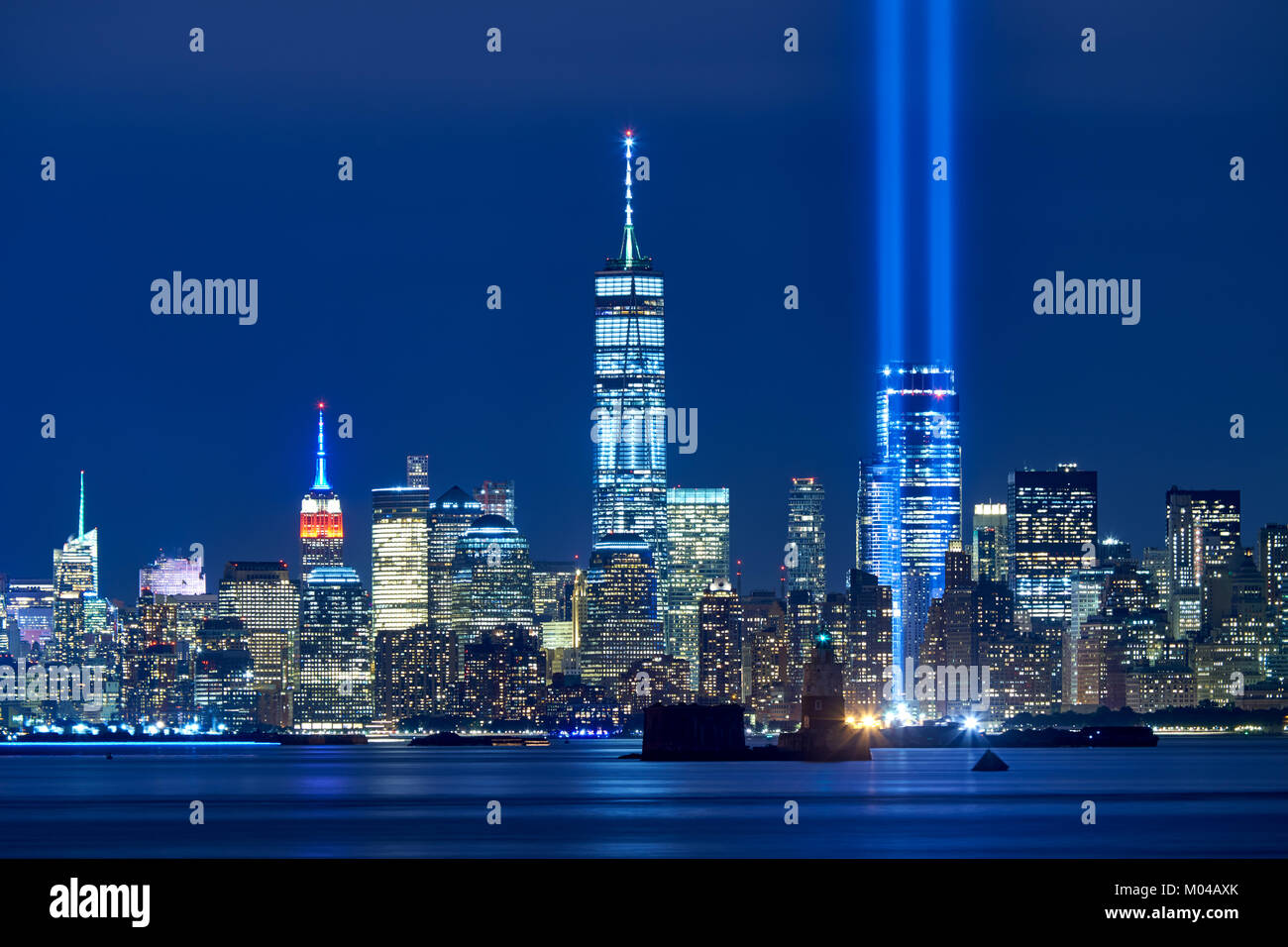 Los dos rayos de luz en el homenaje con skycrapers de Distrito Financiero en la noche. La Lower Manhattan, Ciudad Imagen De Stock