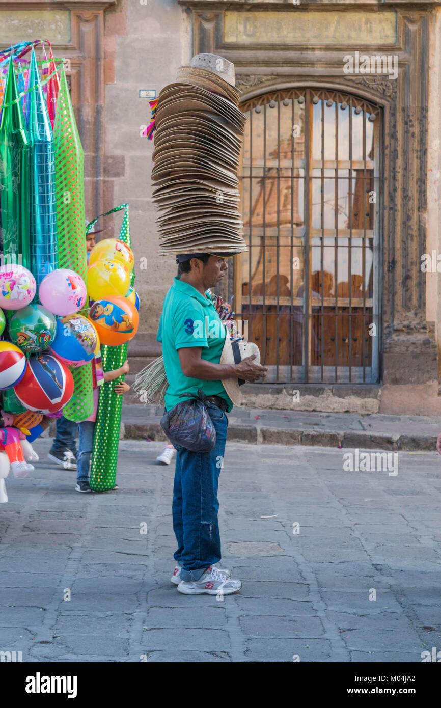 Vendedor Callejero Masculino de pie en una calle de piedra con una pila alta de sombreros de paja sobre su cabeza, Imagen De Stock