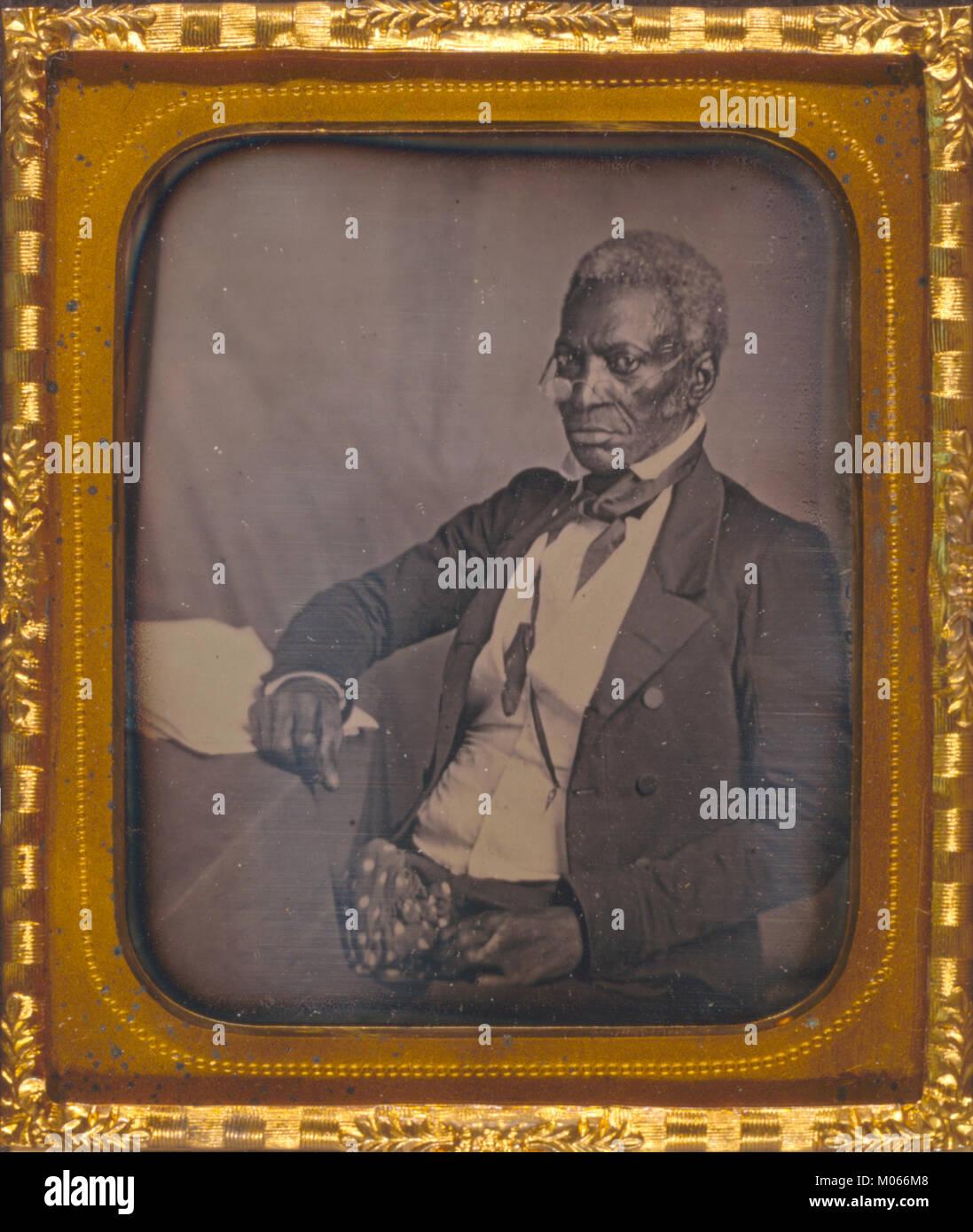 John Hanson, tres cuartos de longitud vertical, tres cuartas partes, con gafas, sentado en el escritorio Foto de stock