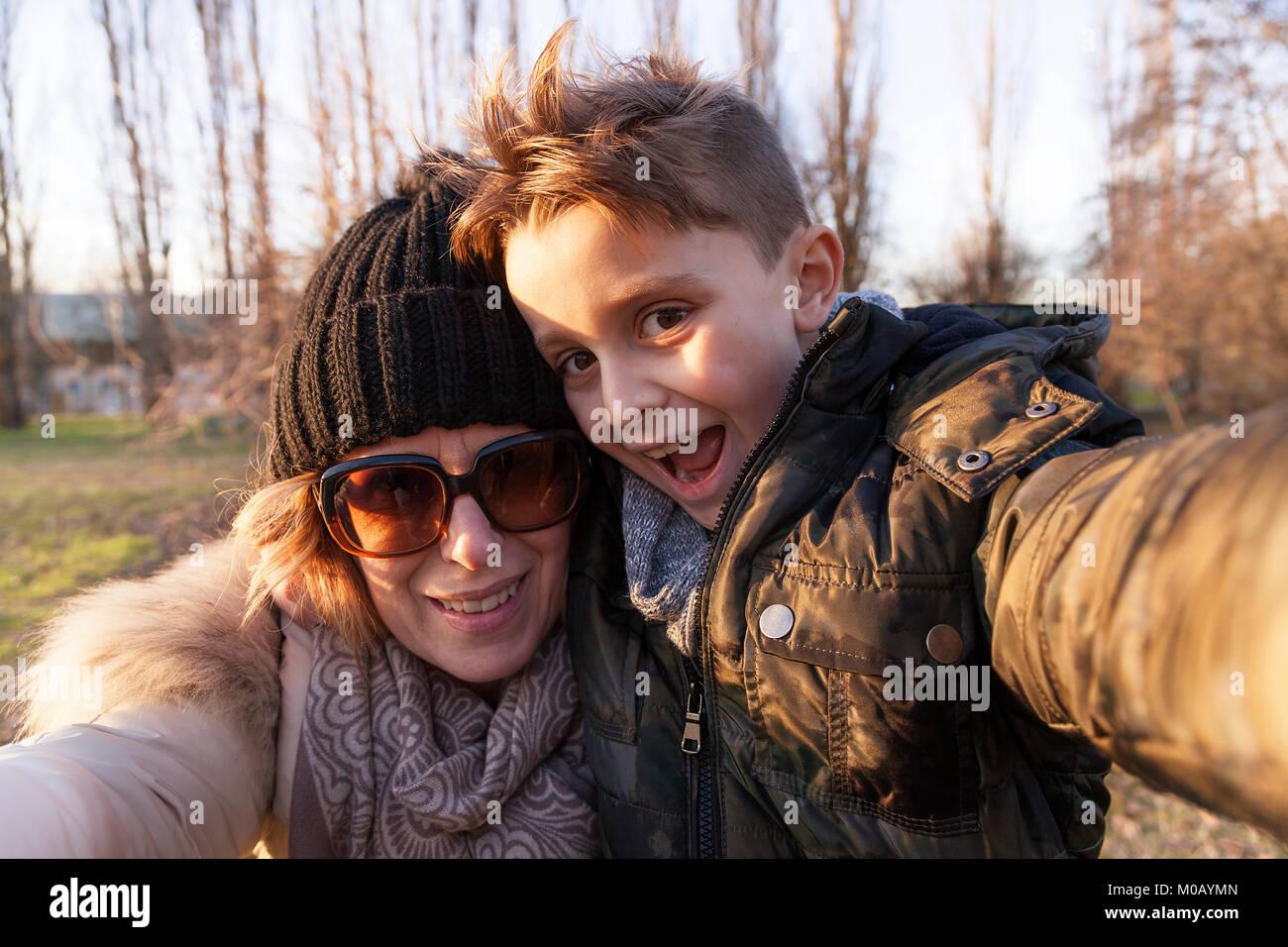 Madre e hijo toma un selfie en un parque público en invierno. Concepto de gente divirtiéndose Imagen De Stock