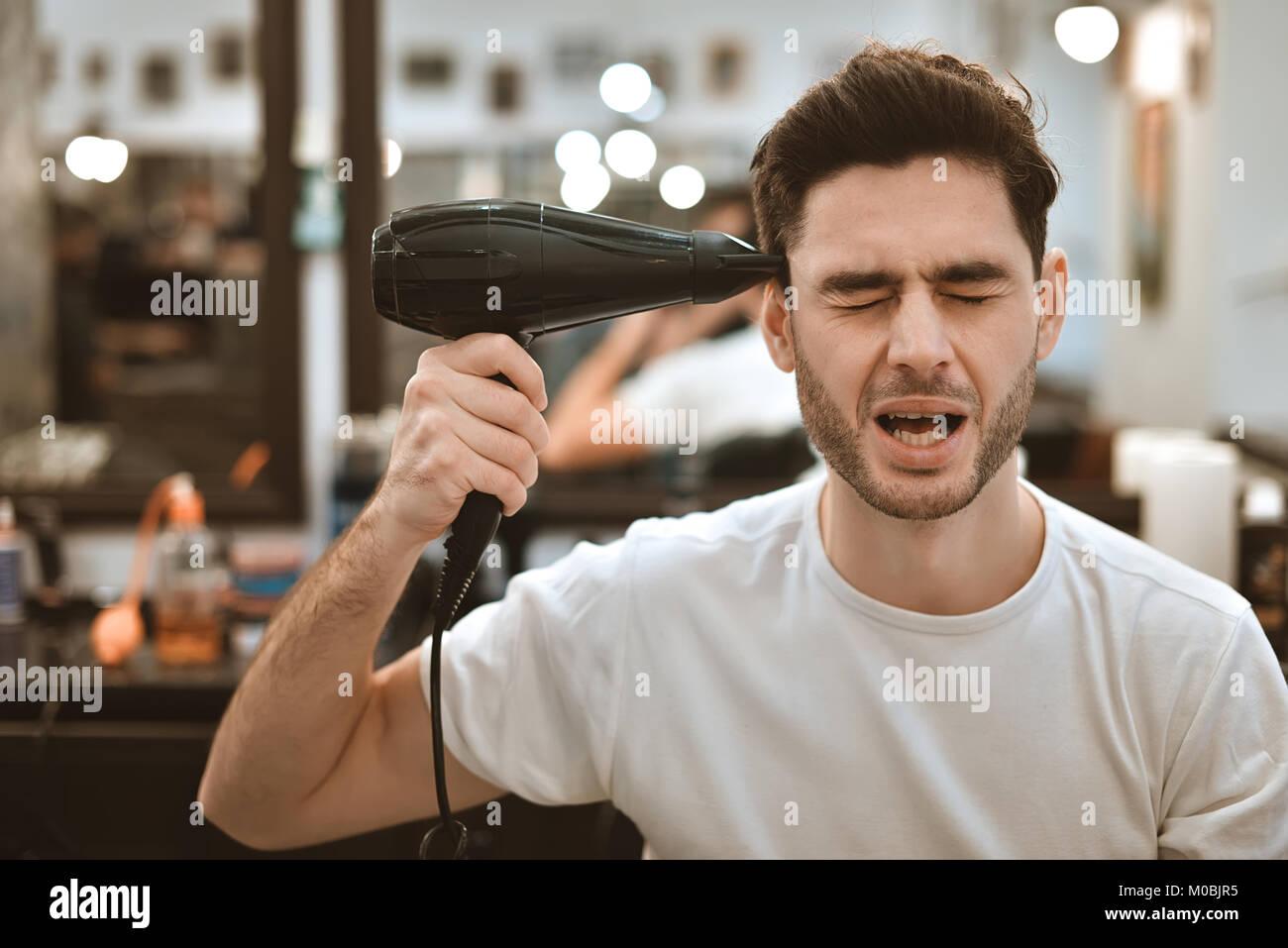 Loco joven hombre elegante con secador de pelo y graciosas expresiones en la barbería. Imagen De Stock
