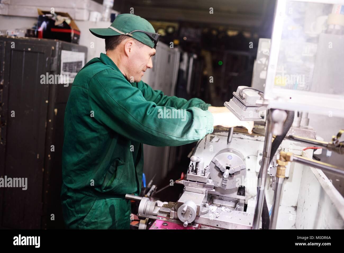 Hombre trabajando en monos de trabajo Imagen De Stock