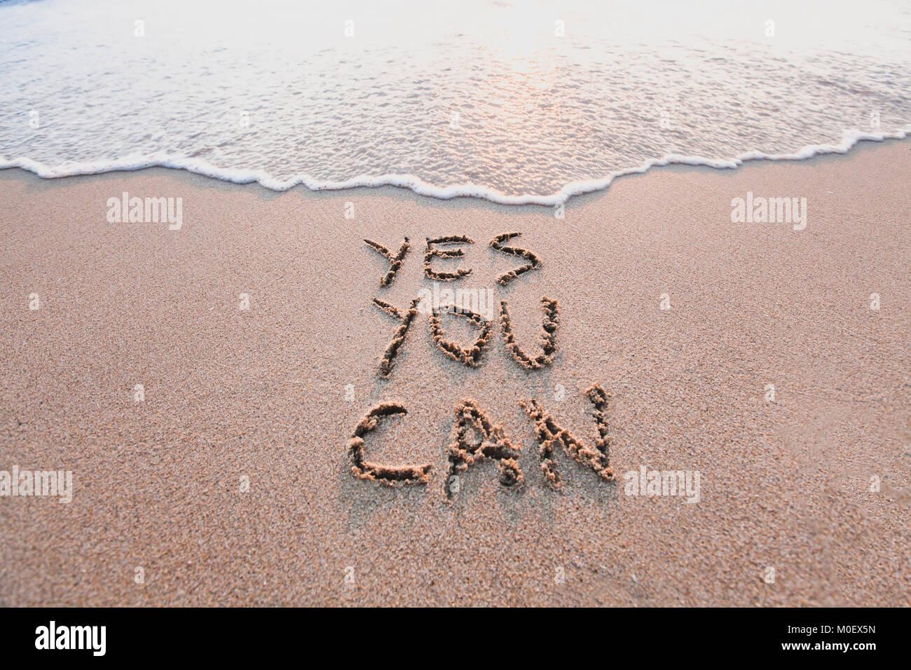 Sí se puede, de motivación concepto inspirador mensaje escrito en la arena de playa. Imagen De Stock