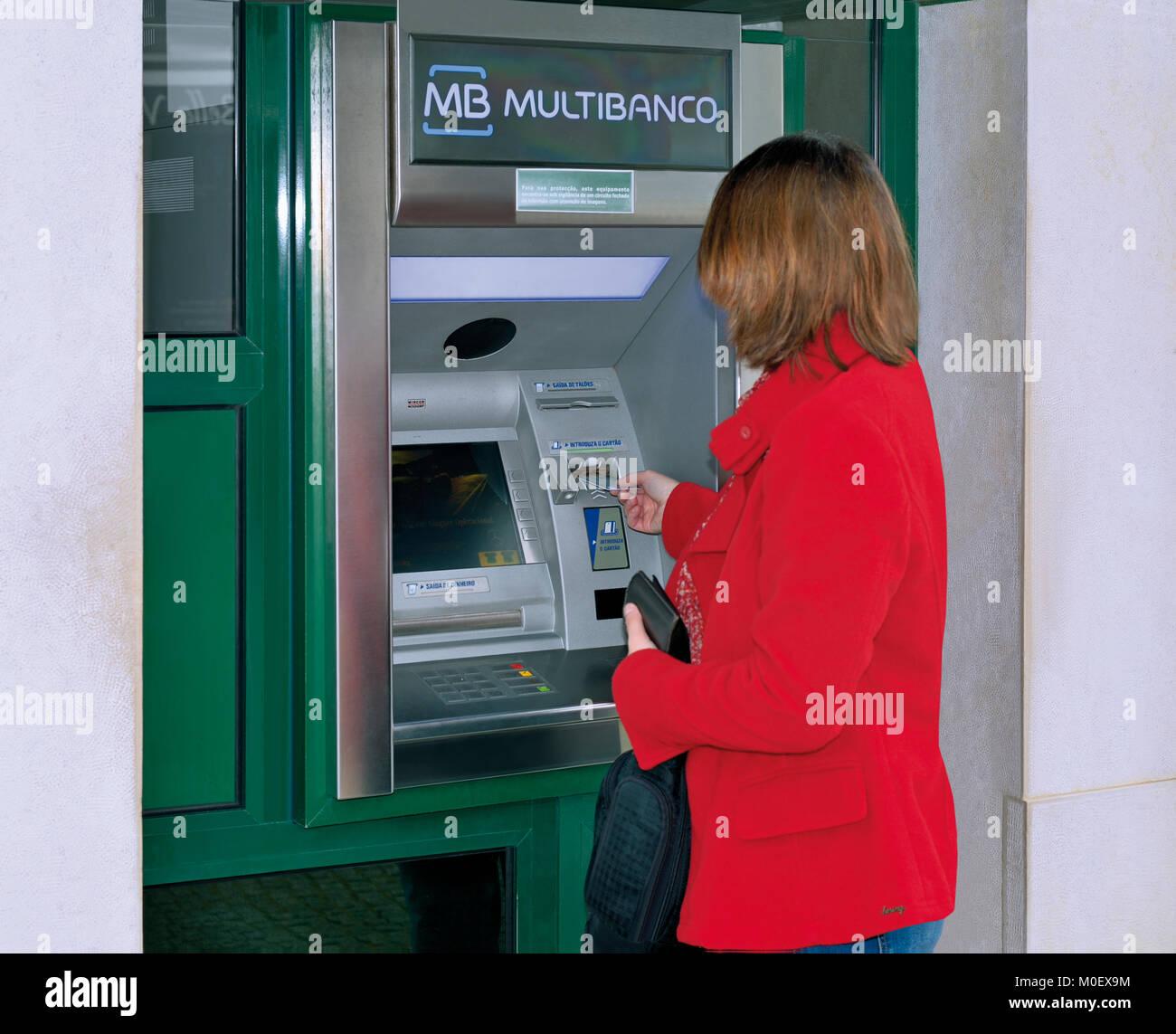 Mujer con tarjeta bancaria en el cajero automático Imagen De Stock