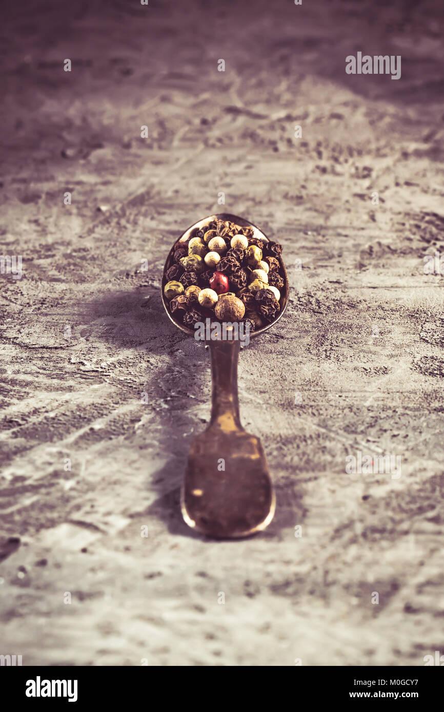 Pimienta guisantes en vintage cuchara en mesa de piedra, la imagen en tonos de moda de estilo rústico de mínima Foto de stock