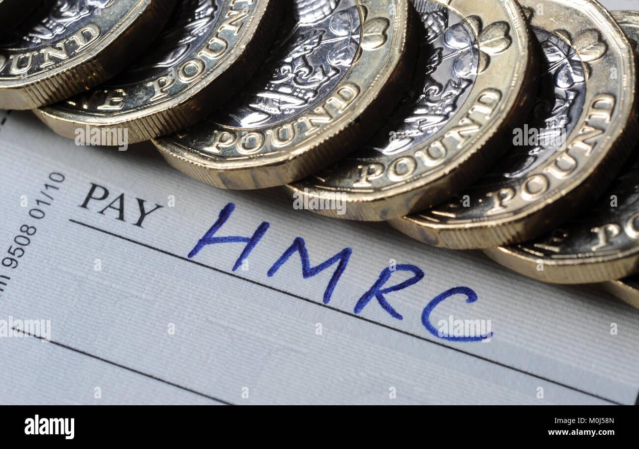 Talonario de cheques y una libra de monedas con el HMRC PAGAR NOMBRE RE Inland Revenue impuestos evasión fiscal Imagen De Stock