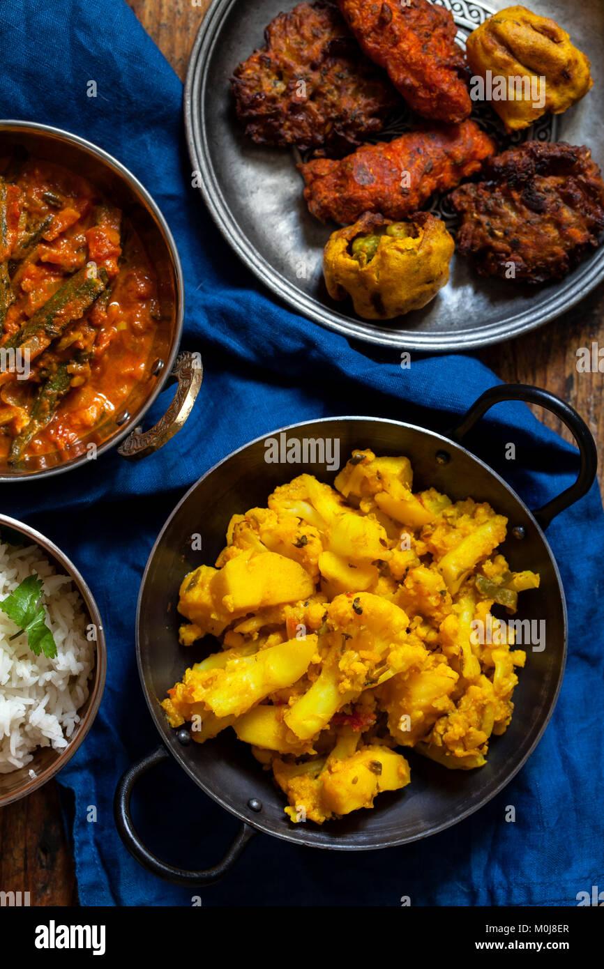 Comida india con okra Aloo Gobi, curry, arroz y pakoras Foto de stock