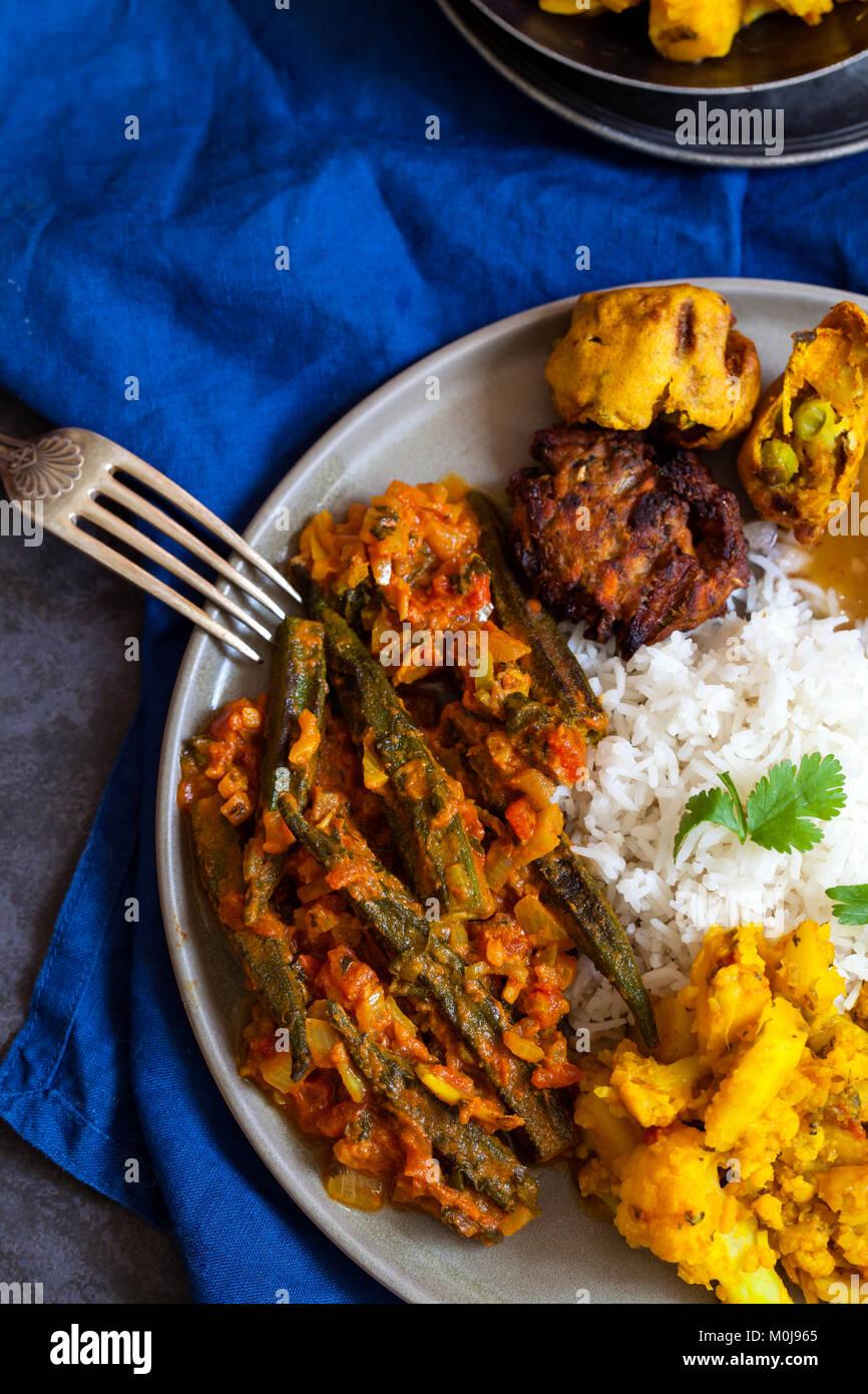 Comida india con okra Aloo Gobi, curry, arroz y pakoras Imagen De Stock