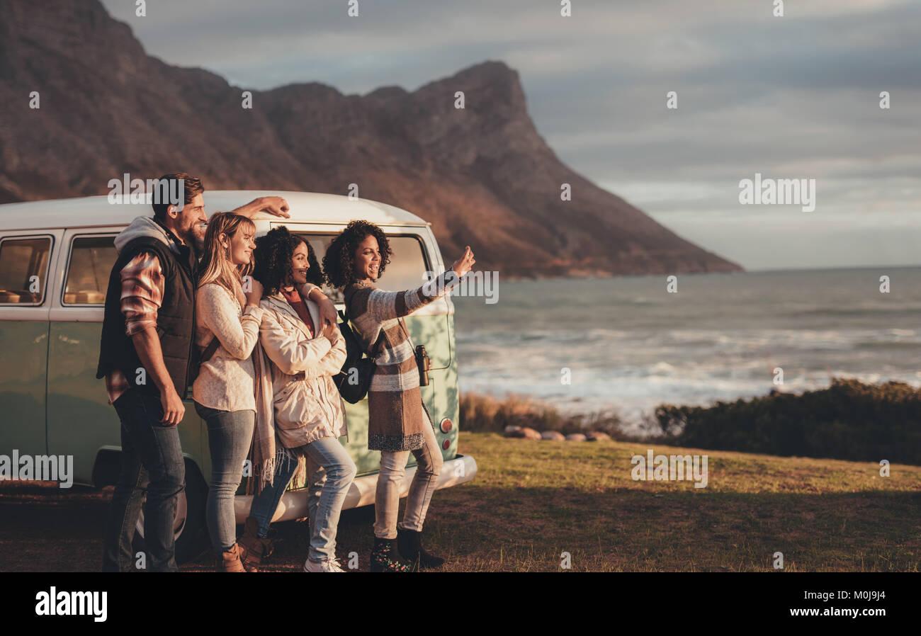 Amigos en viaje por carretera tomando autorretrato con teléfono móvil por la minivan. Grupo de hombre Imagen De Stock