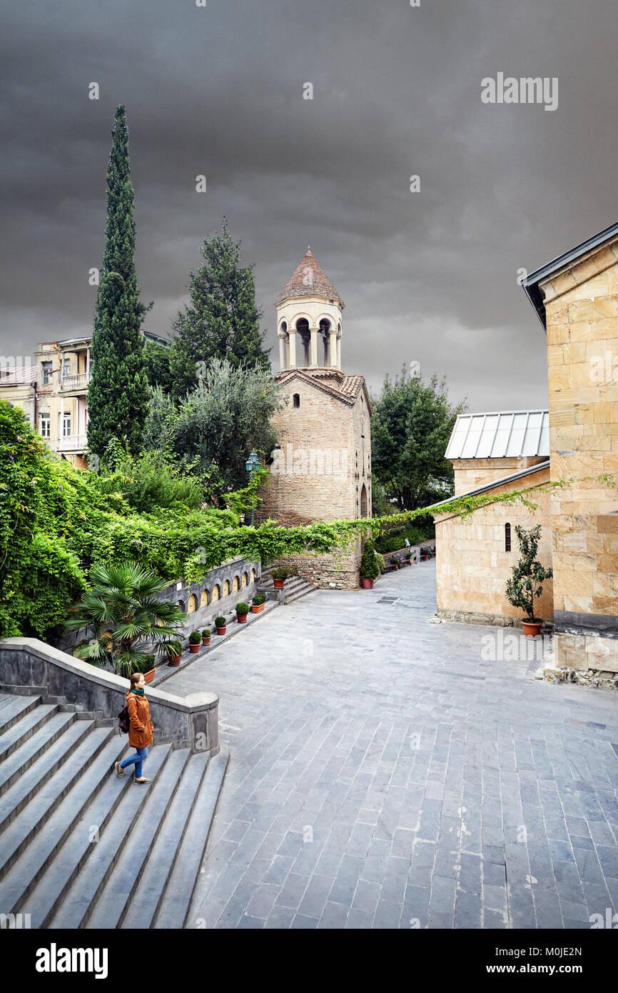Mujer de turística chaqueta marrón caminando por las antiguas calles cerca de Sioni Catedral en el centro Imagen De Stock