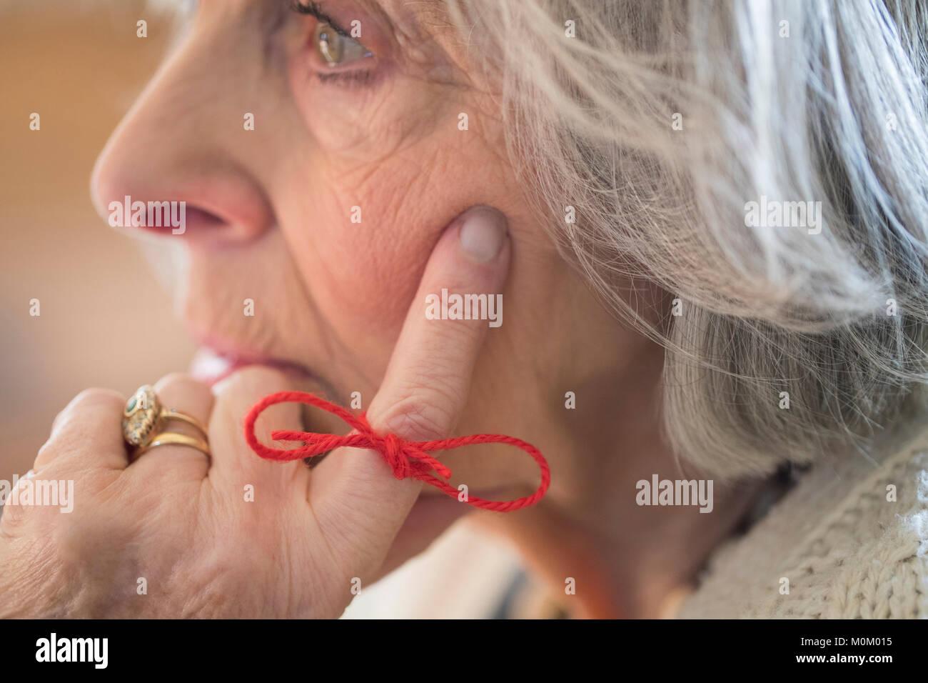Cerca de la mujer de más edad con una cuerda atada alrededor del dedo como recordatorio Imagen De Stock