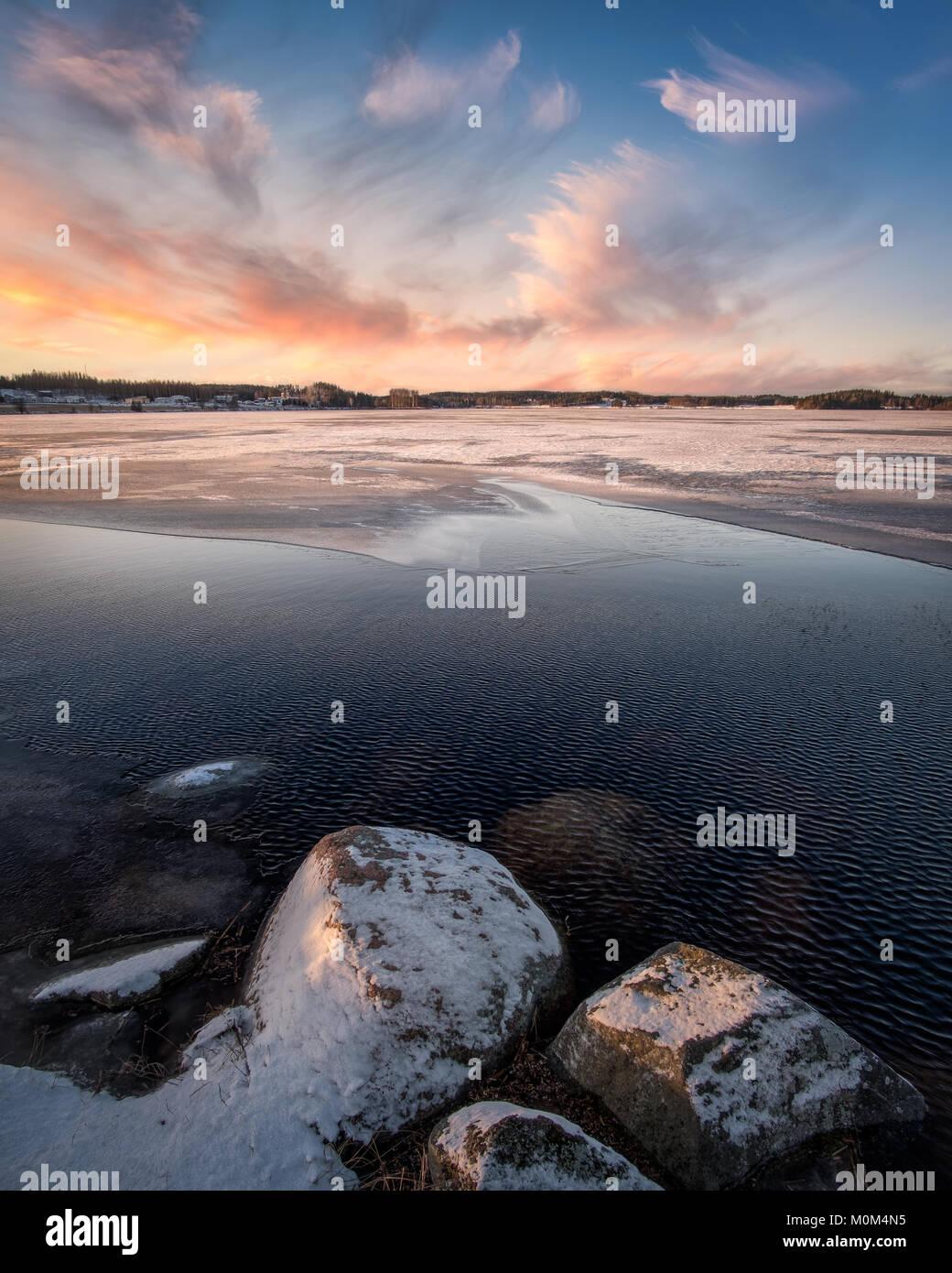 Pintoresco paisaje con puesta de sol y lago congelado en noche de invierno en Finlandia Imagen De Stock