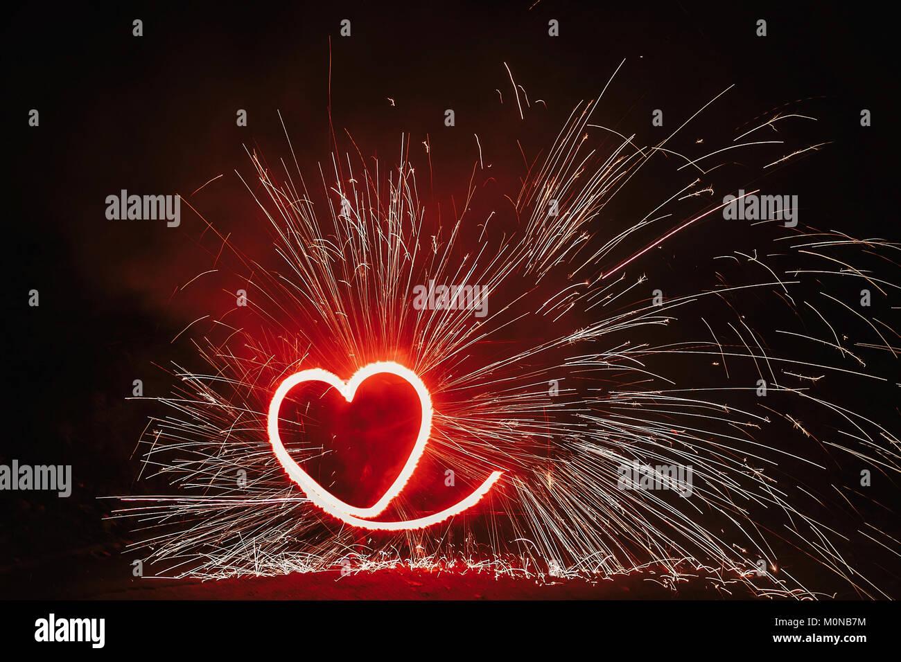 Fuegos artificiales en forma de corazón rojo sobre fondo negro con brillos en la noche. Feliz Día de San Valentín tarjeta corazón ardiente fuego de Bengala. Espacio para texto o boda. Foto de stock
