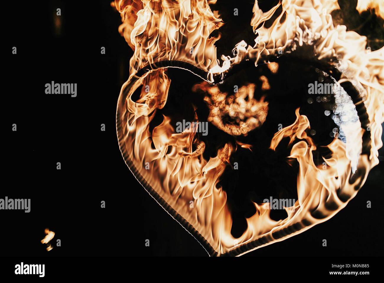 Feliz día de San Valentín card.fuegos artificiales en forma de corazón sobre fondo negro, espectáculo de fuego en la noche. bengala corazón ardiente fuego. Espacio para el texto. Boda o valen Foto de stock