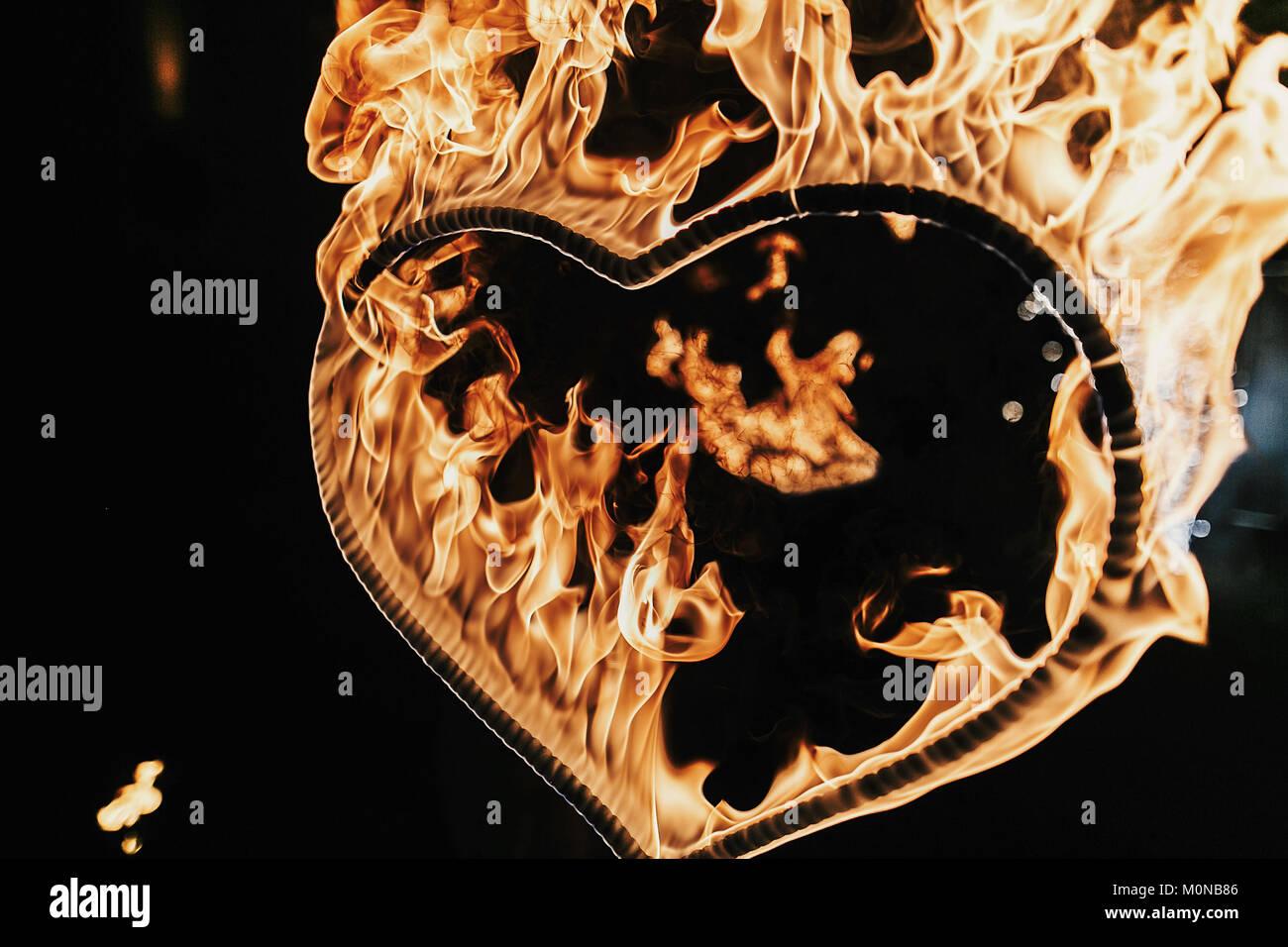 Fuegos artificiales en forma de corazón sobre fondo negro, espectáculo de fuego en la noche. Feliz Día de San Valentín tarjeta corazón ardiente fuego de Bengala. Espacio para el texto. Boda o valen Foto de stock