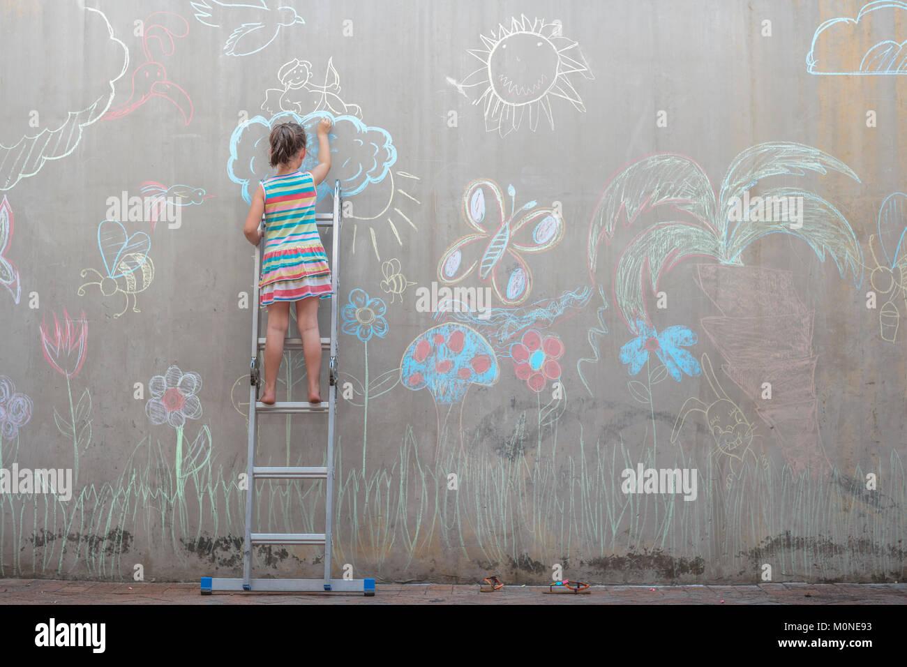 Niña de pie en la escalera coloridas imágenes de dibujo con tiza en una pared de hormigón Imagen De Stock