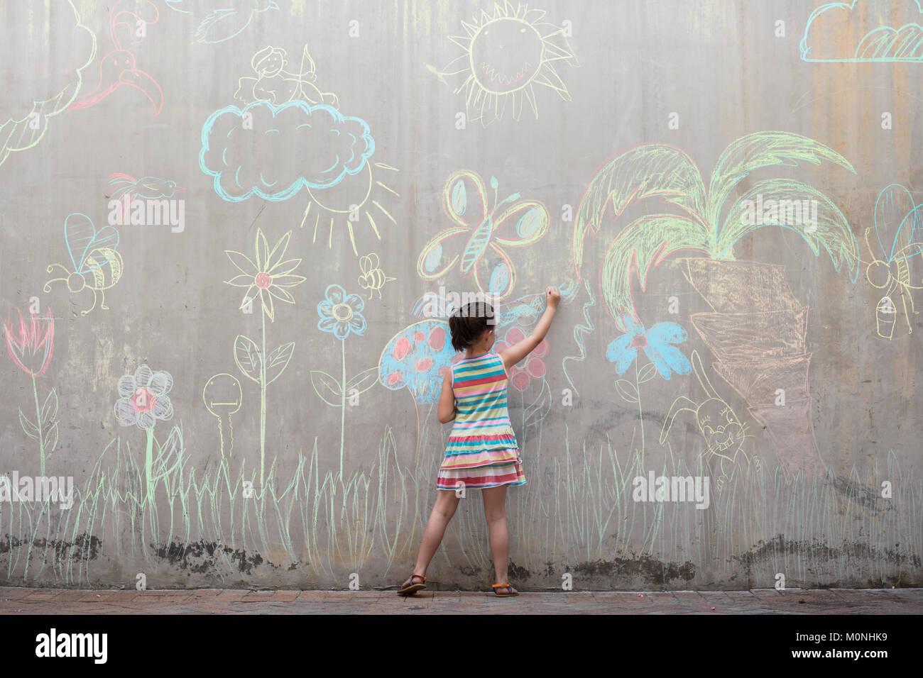 Chica coloridas imágenes de dibujo con tiza en una pared de hormigón Imagen De Stock