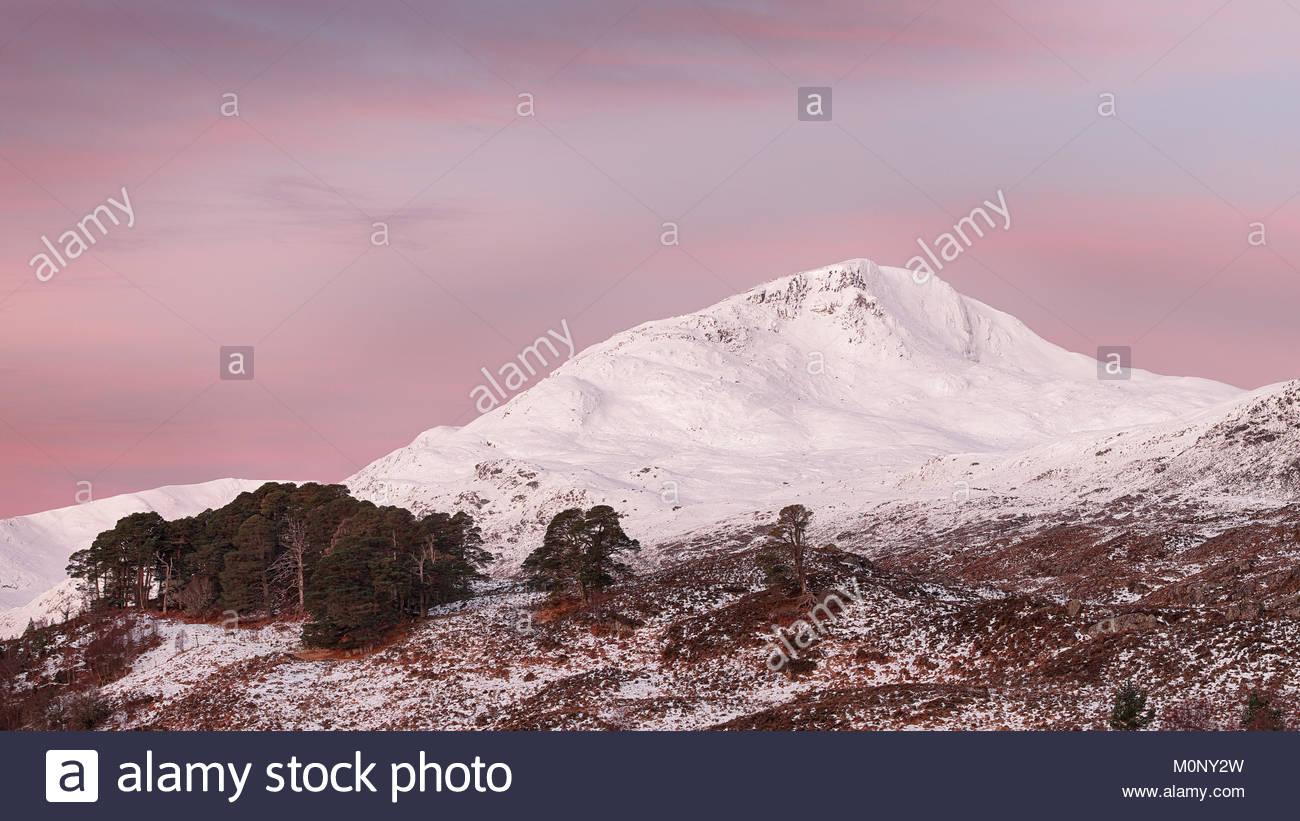 Un colorido Amanecer de Glen Affric en el Scottish highalnds con las montañas cubiertos de nieve Lapaich Sgurr na. Foto de stock