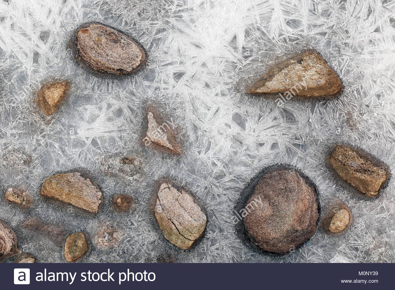 Las rocas congeladas en un cuerpo cubierto de hielo de agua. Foto de stock