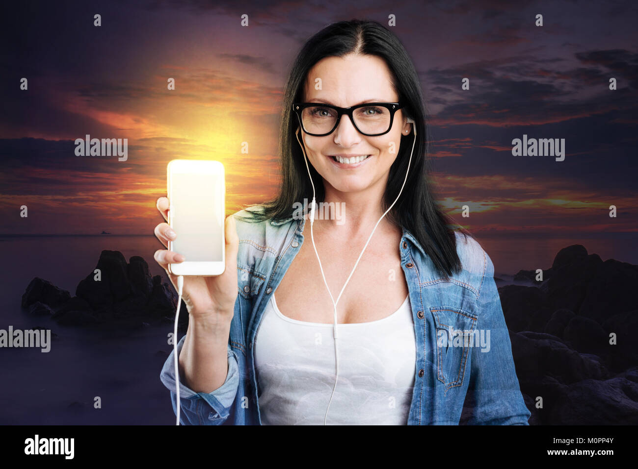Señora sonriente mostrando su smartphone a la cámara Foto de stock