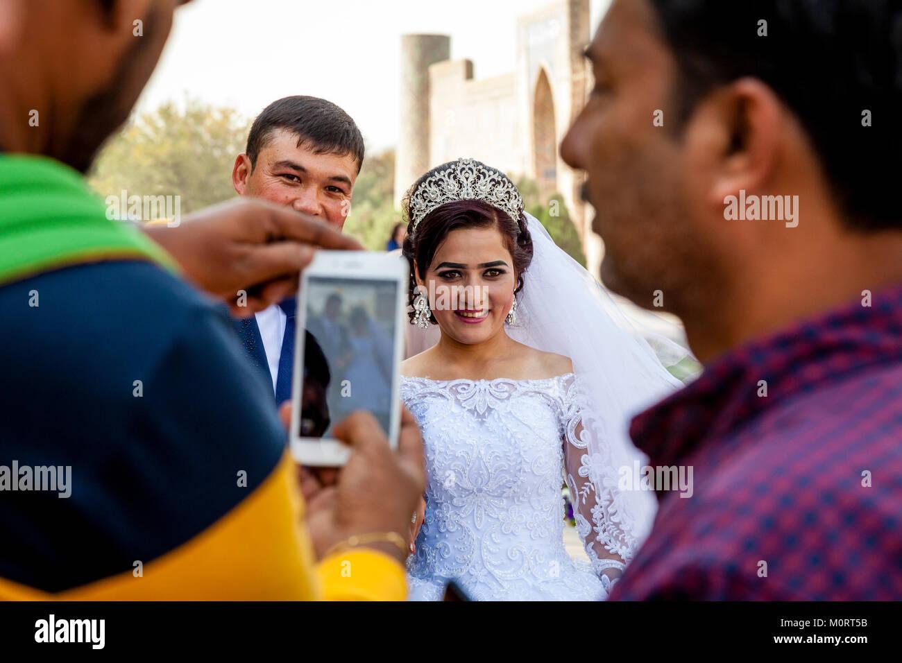 """Los turistas toman fotos de """"Recién casados"""" Pareja joven en el complejo de Registán, Samarcanda, Uzbekistán Foto de stock"""
