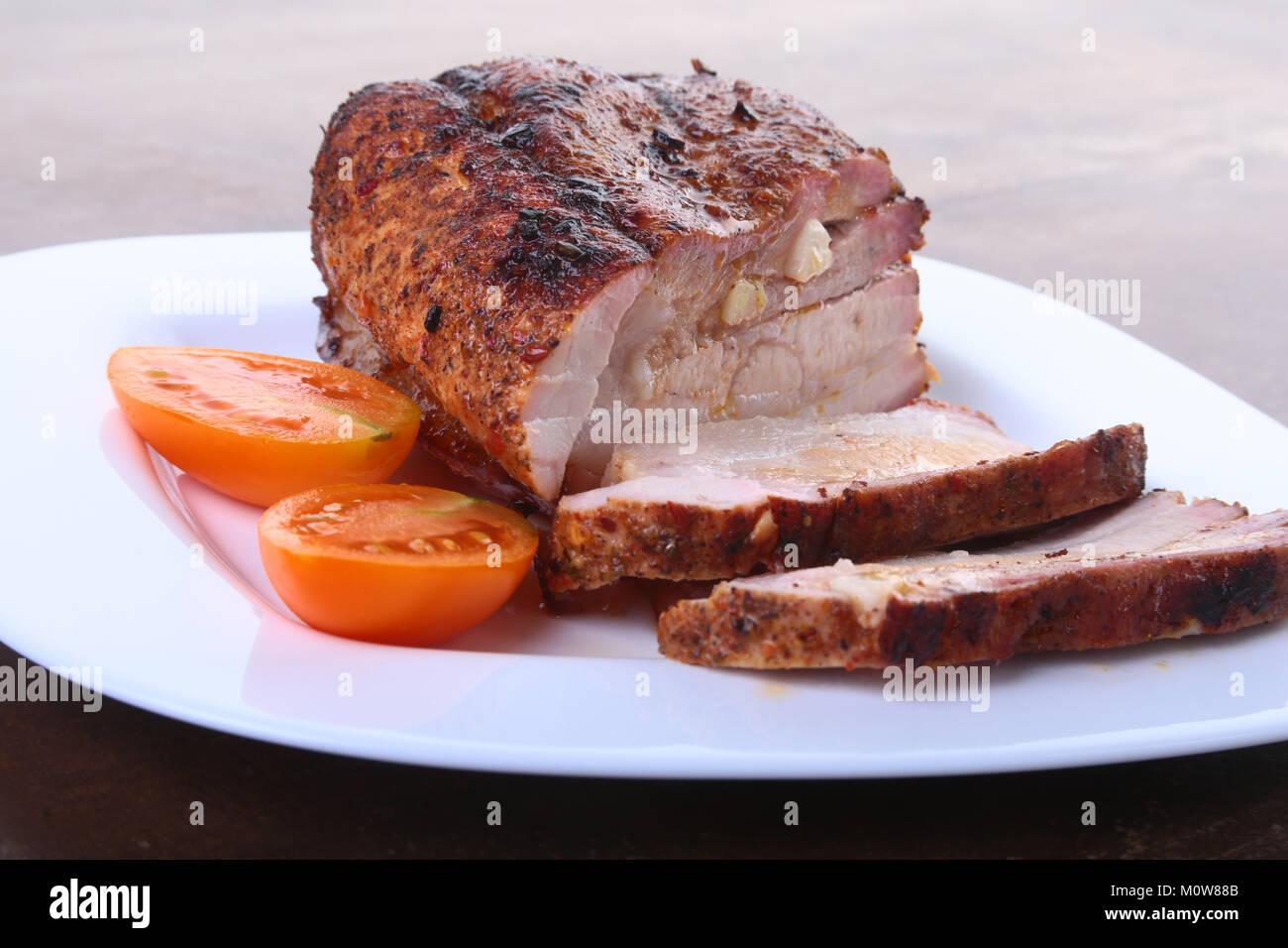 Chuletas de Cerdo Asadas con tomate y salsa de tomate en el plato. Foto de stock