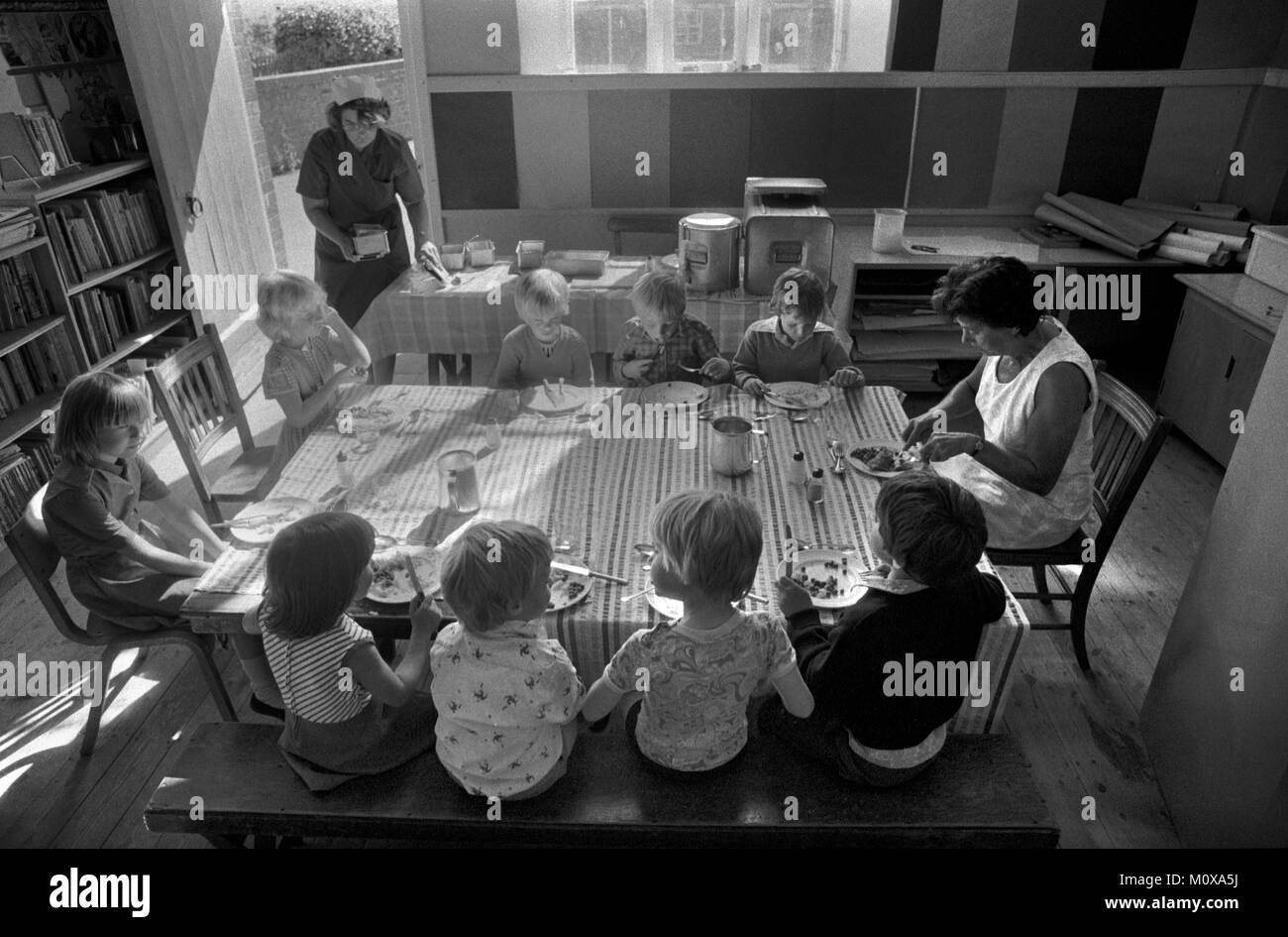 Village Escuela Primaria de los años 70 Inglaterra. Los niños de la escuela se sientan juntos en una mesa con un miembro del personal y almorzar. La cena de la escuela dama en sombrero blanco por mesa larga. Cheveley Cambridgeshire 1978 70 Reino Unido HOMER SYKES Foto de stock