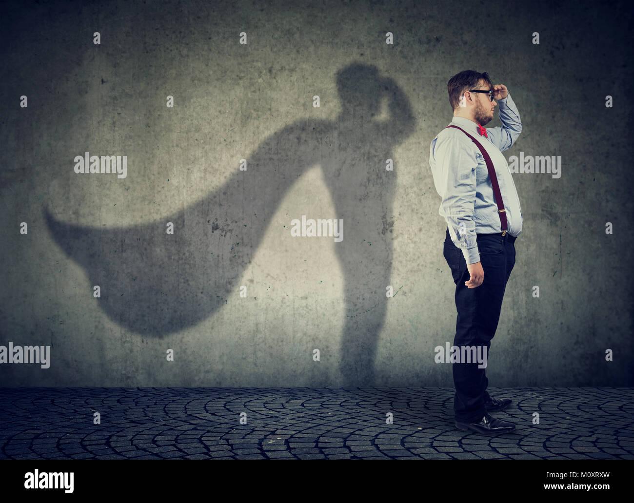 Vista lateral de un hombre gordito imaginándose a ser super héroe busca aspiraban. Imagen De Stock