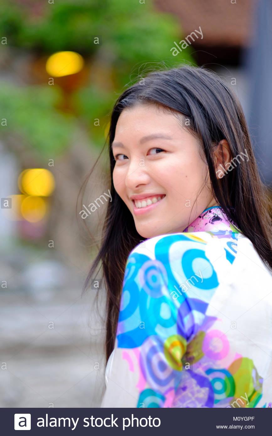 Mujer Vietnamita sonriente y vistiendo un traje tradicional Ao Dai Imagen De Stock