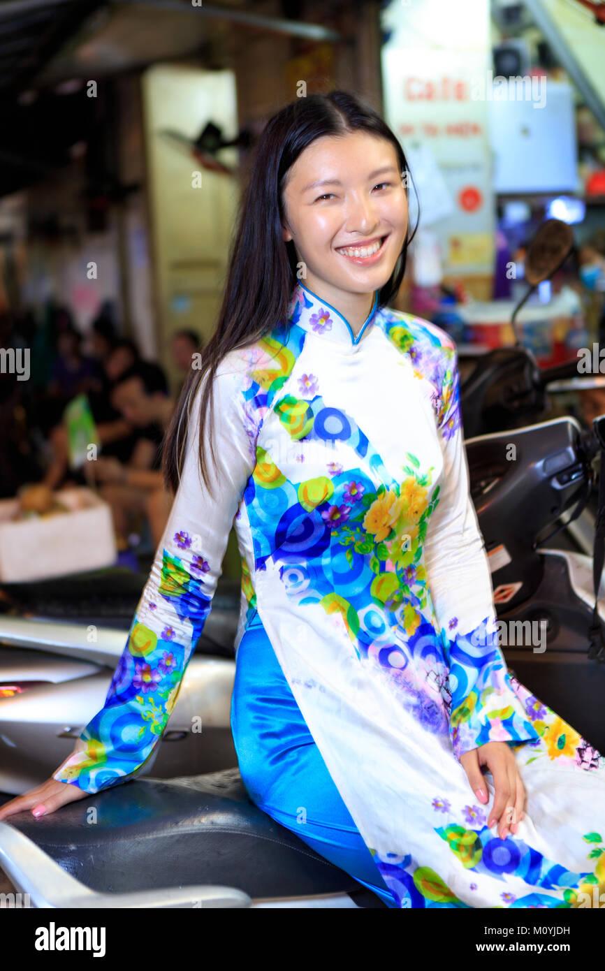 Joven vietnamita sentado en una motocicleta y sonriente en una calle en Hanoi. Imagen De Stock