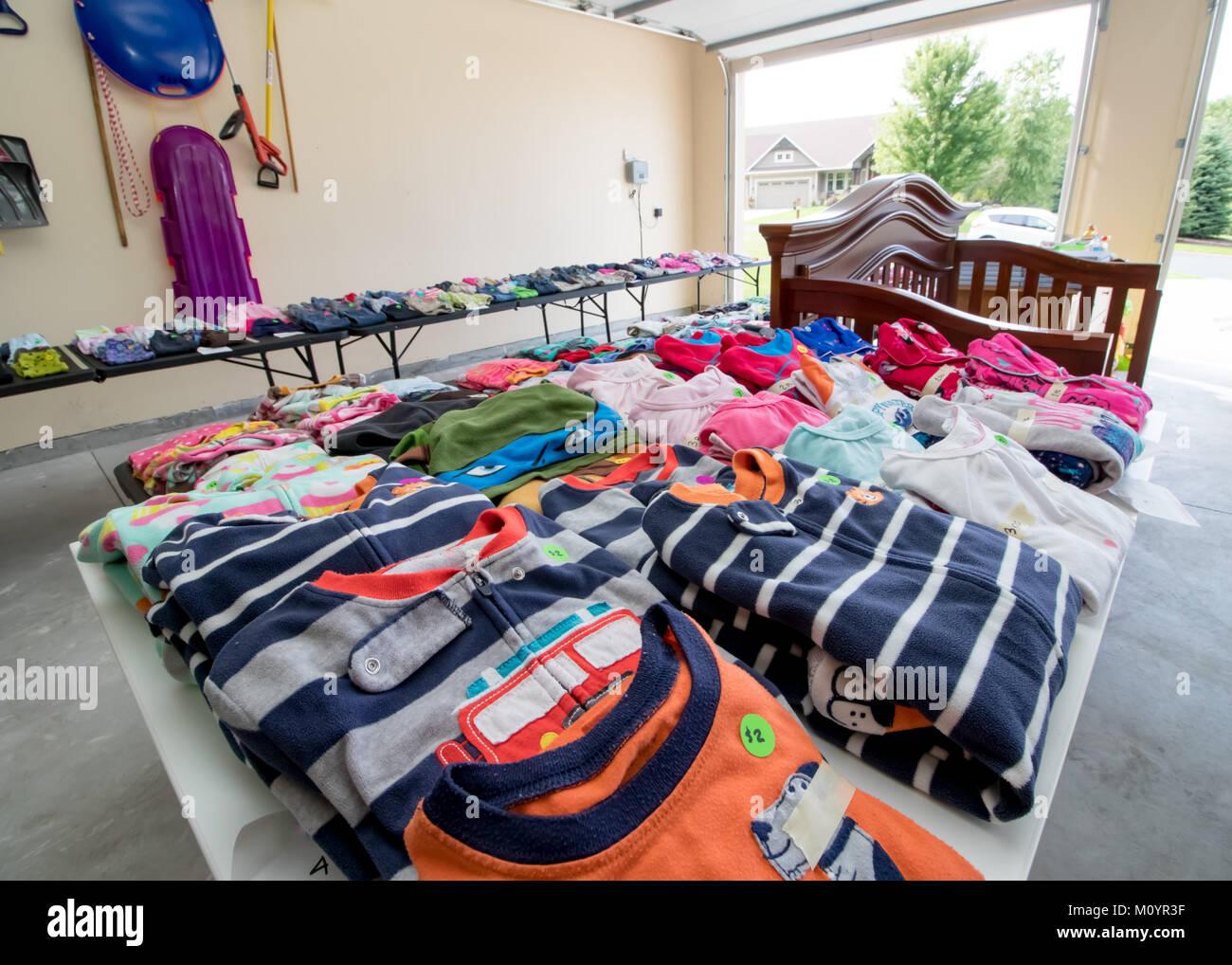 Tablas lleno de platos, juguetes y ropa de niños para venta en un típico americano venta de garaje Imagen De Stock