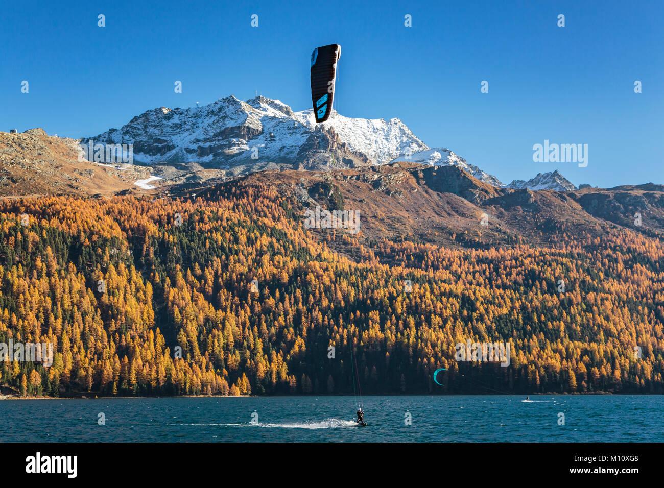 Windsurf en el lago de Silvaplana con follaje de color en los alerces en el valle de Engadin, Graubuden, Suiza, Imagen De Stock
