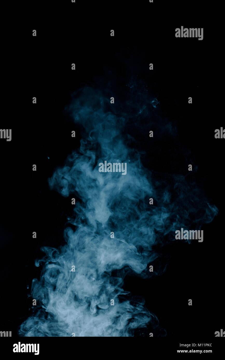 Textura de vapor desde una bebida caliente sobre un fondo negro. Humo azul con espacio de copia. Imagen De Stock
