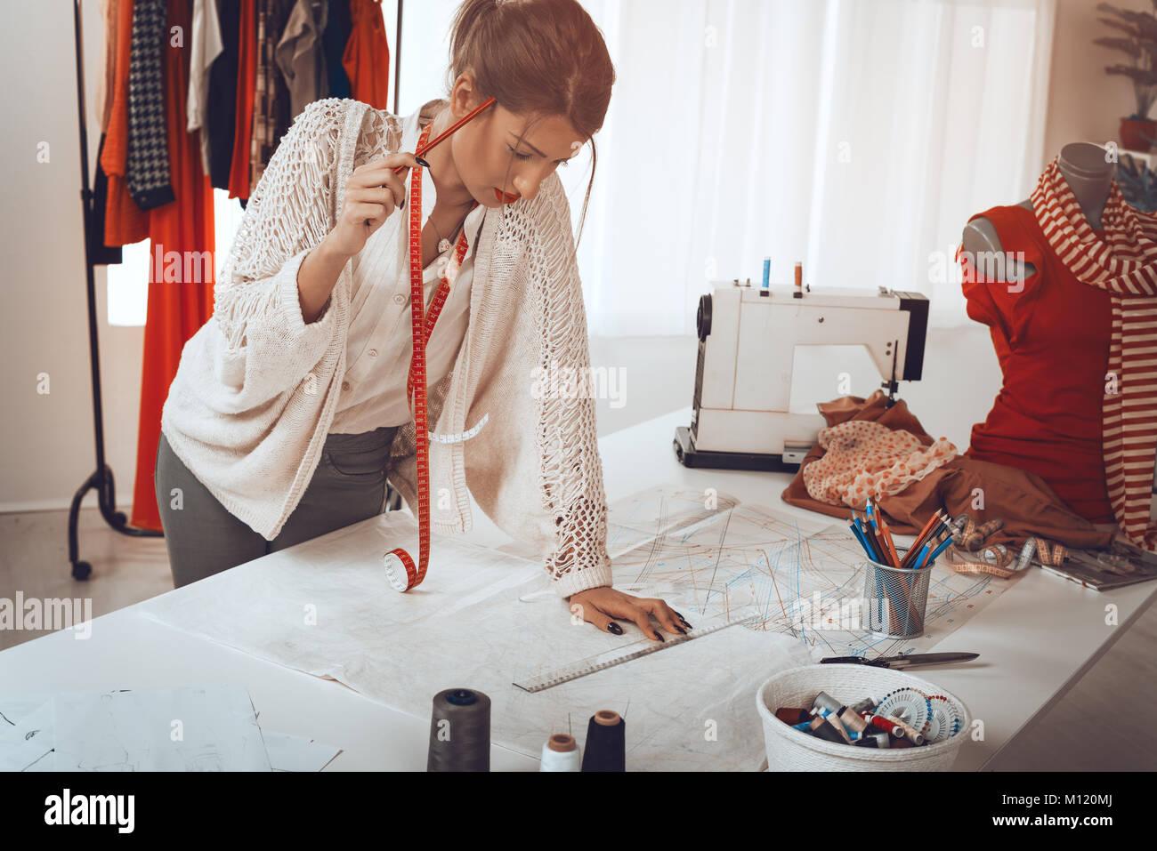 Pensativo joven diseñador de moda femenina con cinta métrica tapaba ...