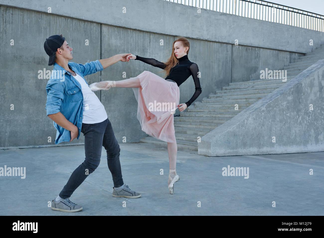 Una esbelta bailarina baila con una bailarina moderna. Fecha de amantes. Desempeño en las calles de la ciudad. Imagen De Stock