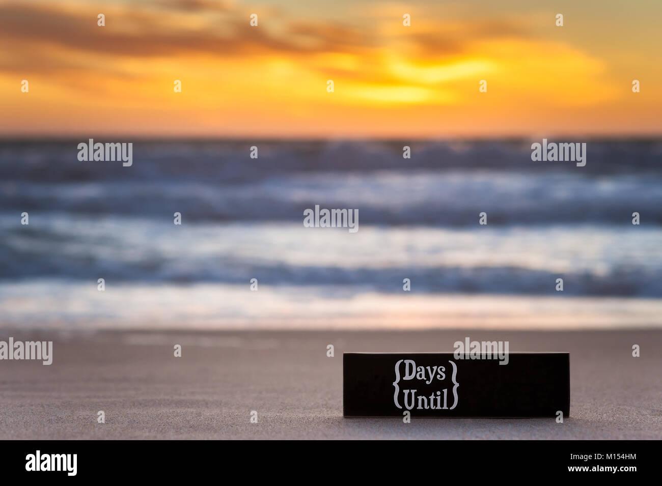 Fotografía horizontal de una cuenta regresiva del calendario signo de la pizarra en la playa con el océano Imagen De Stock