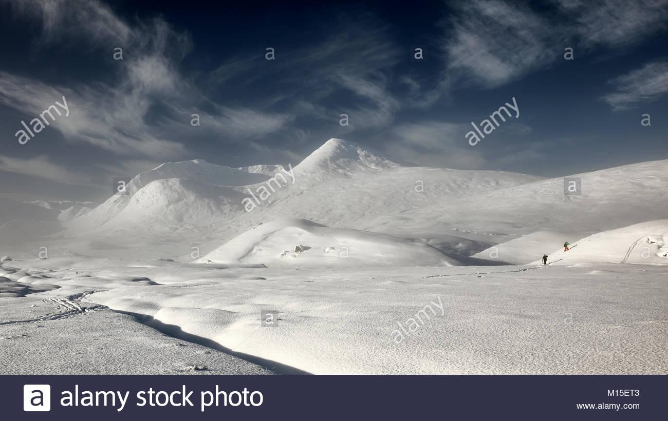 Una cubierta de nieve y misty Rannoch Moor mirando a la cordillera Blackmount con dos esquiadores en la distancia Foto de stock