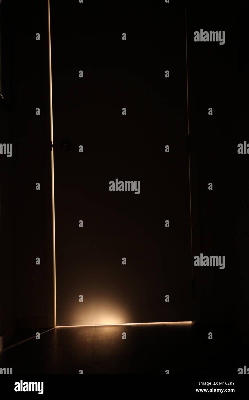 Luz detrás de la puerta entreabierta, drama Foto de stock
