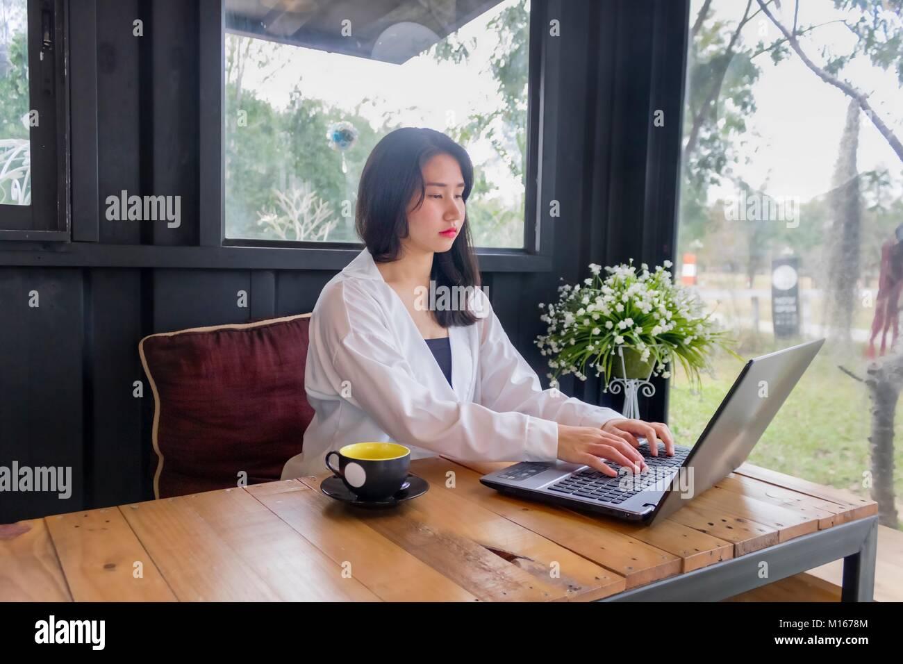 Una Chica Asiatica Con La Camisa Blanca Juega Notebook Sobre Mesa De Madera En La Habitacion Negra Fotografia De Stock Alamy