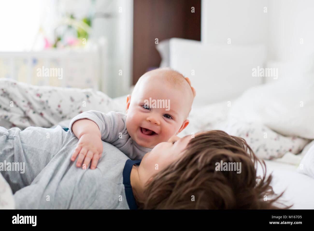 Dos niños, el bebé y su hermano mayor en la cama en la mañana, jugar juntos, reír y pasar un buen rato, compartir Foto de stock