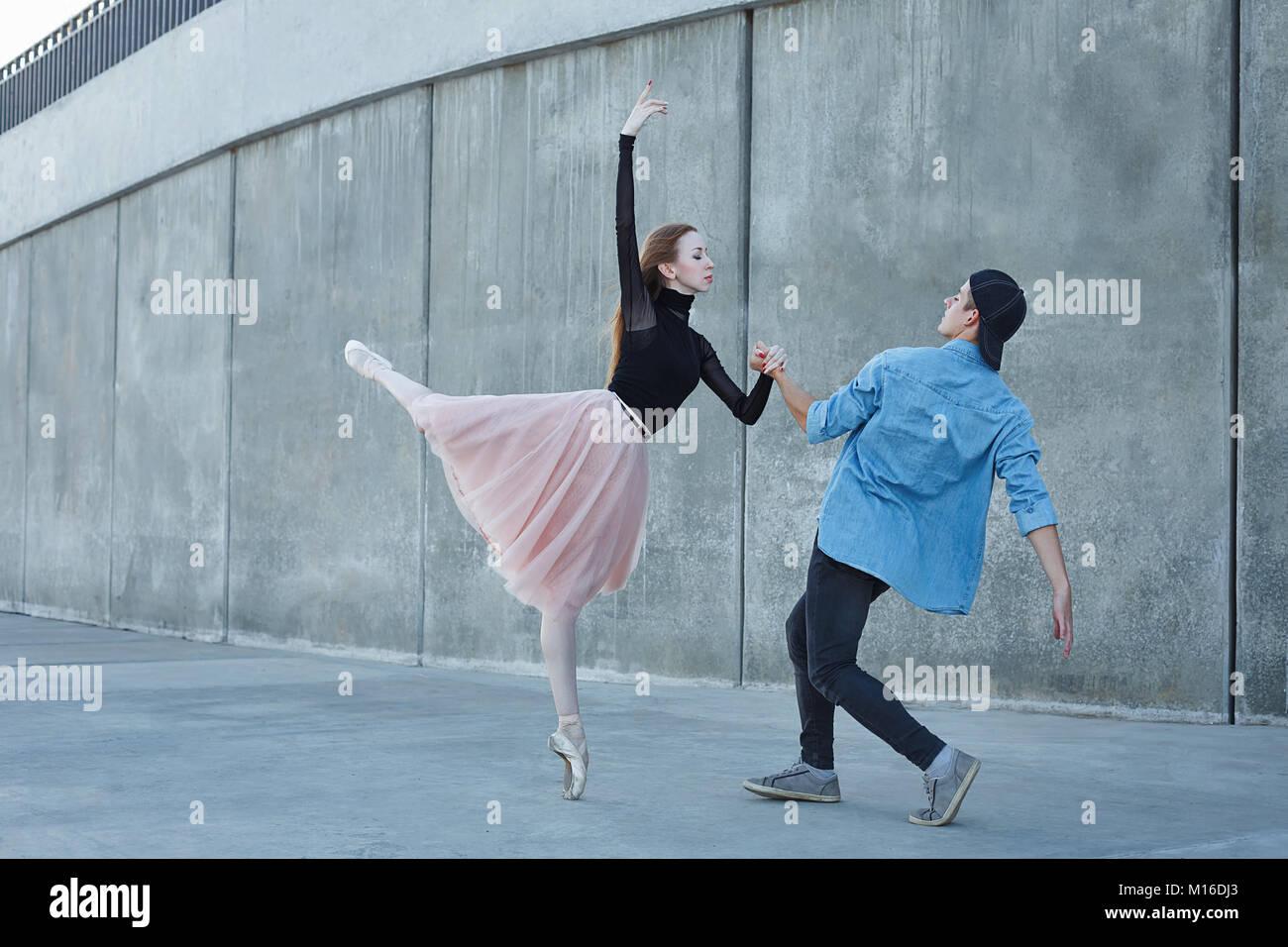Esbelta bailarina baila con una bailarina moderna. Fecha de amantes. Desempeño en las calles de la ciudad. Imagen De Stock